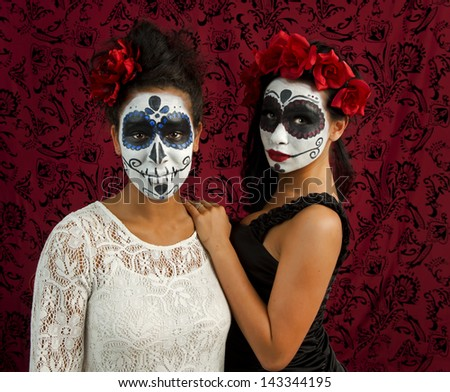 Two beautiful young women with sugar skulls comfort each other. - stock photo
