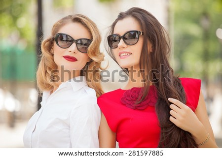 Two Beautiful youngs women with sunglasses walking in the city. Summer photo - stock photo