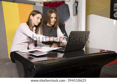 Two beauty young adult businesswomen at office working with laptop