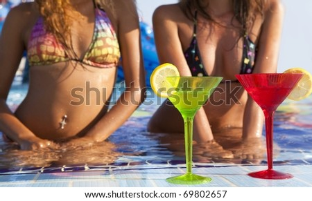 Two beautyful  women enjoying teir summer vacation with a glasses of martini - stock photo