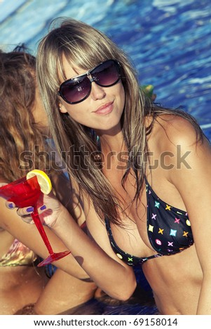 Two beautyful women enjoying their summer vacation with a glasses of martini - stock photo