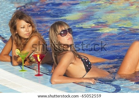 Two beautyfull  women enjoying teir summer vacation with a glasses of martini - stock photo