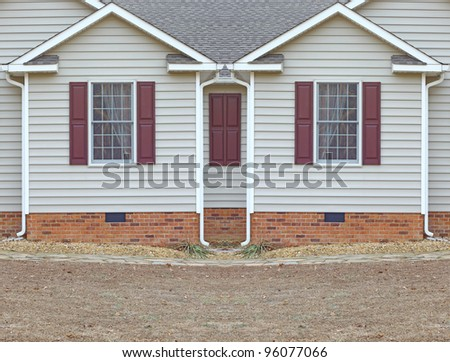 Two bedroom windows in a vinyl sided house with a curtains in them on a brick foundation along with gutters on both sides with room for your text. - stock photo