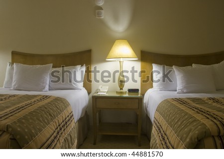 Two beds bedroom with bedside table and lamp - stock photo