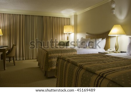 Two beds bedroom with bedside table and three lamps - stock photo