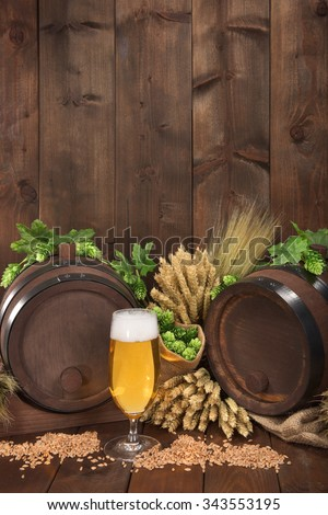 two beer barrels with beer glass, hops, wheat, grain, barley and malt - stock photo