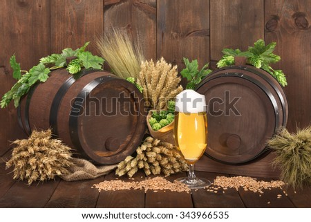 two beer barrels with beer glass, hops, wheat, grain, barley and malt