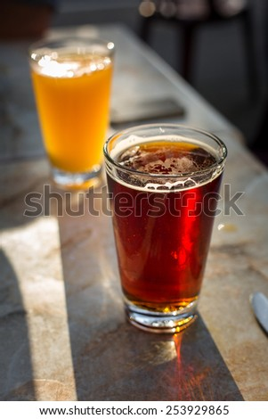 Two beer glasses on a table in the setting sun in San Francisco, California.
