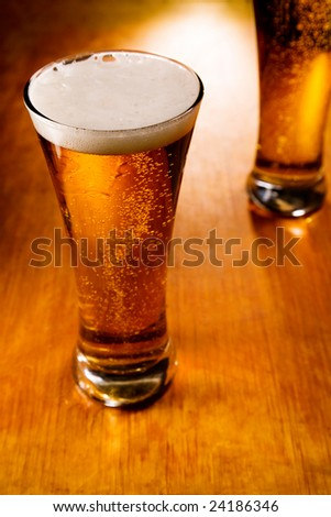 Two beer glasses on wood background, selective focus - stock photo