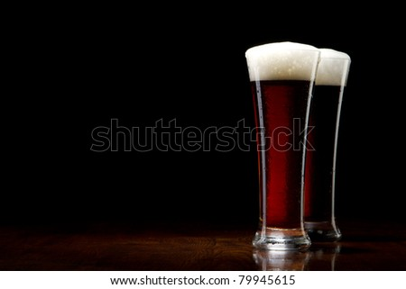 two Beer into glass on a black and wooden table