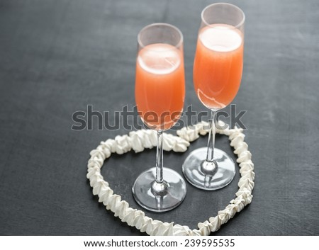 Two bellini cocktails inside of meringue heart - stock photo