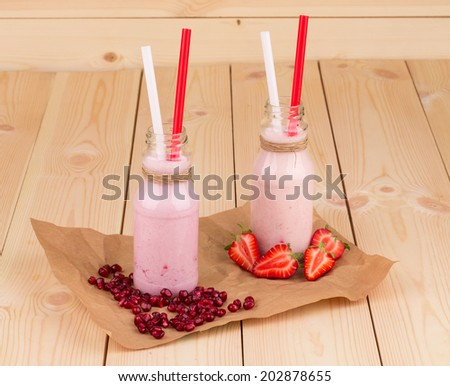 Two berry smoothie present in a little milk bottles - stock photo