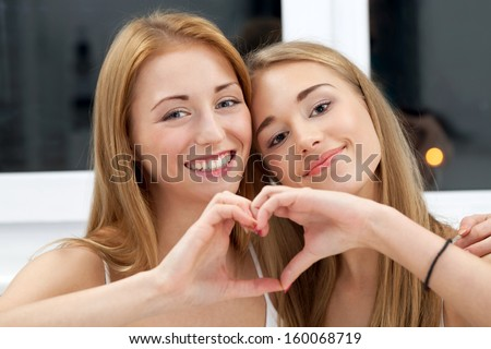 Two best friends showing their common heart - stock photo