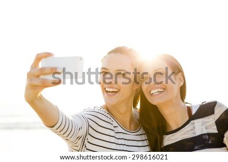 Two best friends taking a selfie with cellphone