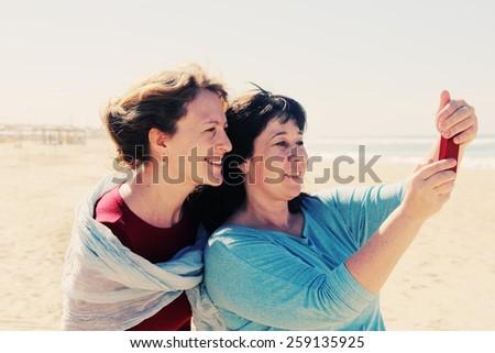 two best friends walking at seaside - stock photo