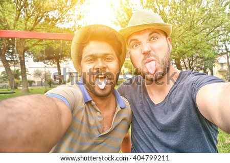 Two best multiracial friends taking selfie with mobile phone camera - Young multi ethnic people having fun making funny faces - Interracial friendship concept - Warm filter with artificial sunlight - stock photo