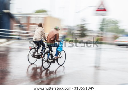 two bicycle riders on the move in the city while it is raining - stock photo