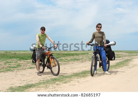two bicycle tourists standing on road, blue sky and horizon - stock photo