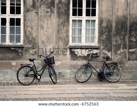 two bicycles in front of grunge wall - stock photo