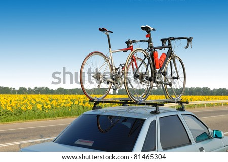 two bicycles mounted on roof of car against sky - stock photo