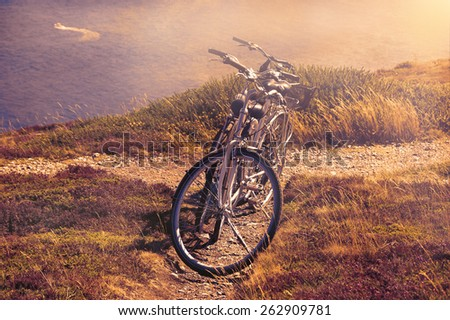 Two bicycles on the hill over the sea in sunny day and a boat sailing at background. Breton coast near Cap de la Chevre. Brittany, France. Active summer vacation background. Toned photo. - stock photo