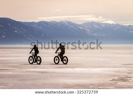 Two bicyclists ride fat tire bikes across a frozen Flathead lake with the Mission Mountain range in the background near Kalispell MT. - stock photo