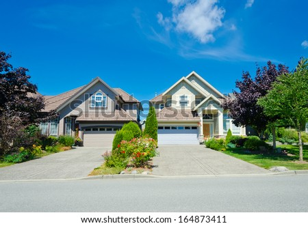 Two big custom made luxury houses with nicely trimmed and landscaped front yards and wide and long driveways in the suburbs of Vancouver, Canada. - stock photo