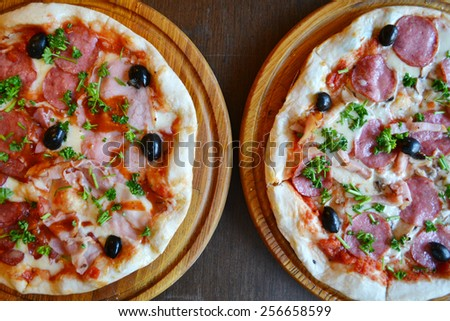 Two big hot and tasty pizzas with olives and salami - stock photo