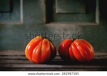 Two big red tomatoes RAF over old wooden table. Dark rustic atmosphere - stock photo