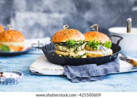 Two Big sandwich - hamburgers with juicy chicken burger, cheese, basil, and yogurt sauce on white wooden table. Rustic blue table.  - stock photo
