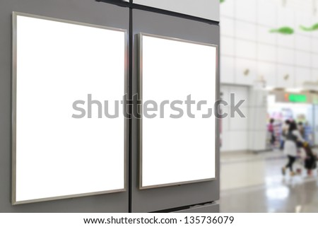 Two big vertical / portrait orientation blank billboard on wall in public open space with blurred shop background - stock photo