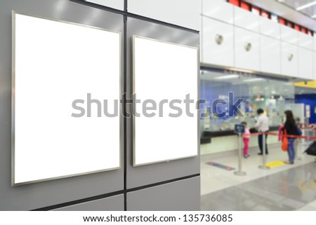 Two big vertical / portrait orientation blank billboard on wall in public open space with passenger background