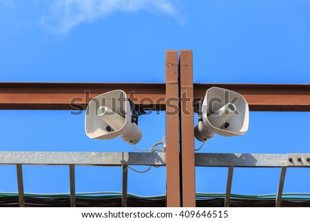 Two big white loudspeakers on the brown metal construction - stock photo