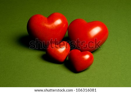Two bigger and two smaller hearts on a green background - stock photo