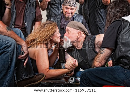 Two biker gang lovers kiss while arm wrestling