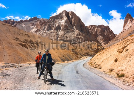 Two bikers are standing on Himalayas mountain road