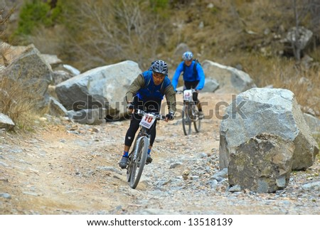 Two bikers downhill on old rural road in desert mountains - stock photo