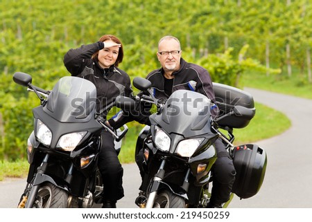 Two bikers on their motorcycles look straight ahead - stock photo