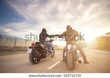 Two bikers ot motocycles handshaking with knuckle on road at sunshine - stock photo