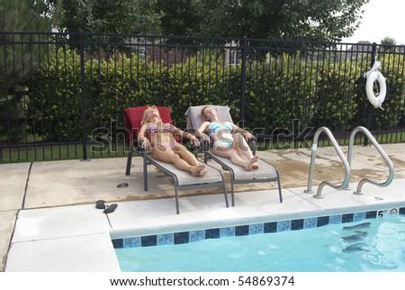 Two Bikini Blond Women Poolside - stock photo