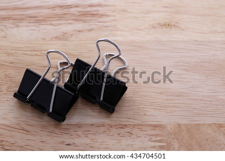 Two Binder Paper clip on wooden background