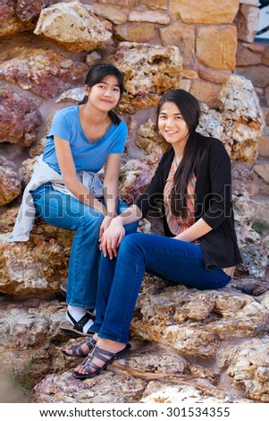 Two biracial  young teen girls, sisters or friends,  sitting together on rocky stone seats outdoors - stock photo