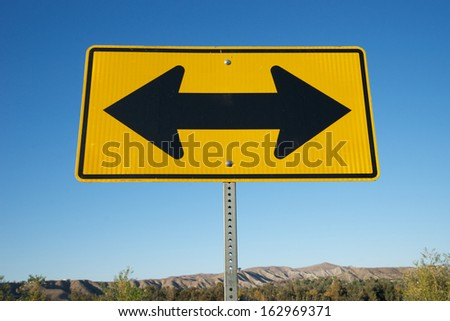 Two black arrows on a yellow metal road sign signify making decisions in life. - stock photo