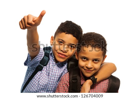 Two black boys after school with thumbs up and hugging each other - stock photo