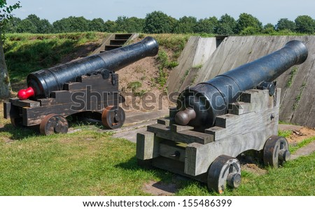 Two black canons at fortress Bourtange in the Province Groningen - stock photo