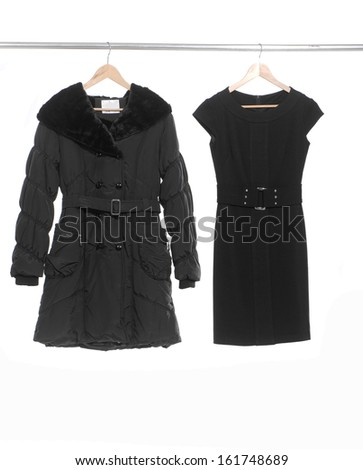 Two black evening and coat female clothing on a hanger  - stock photo