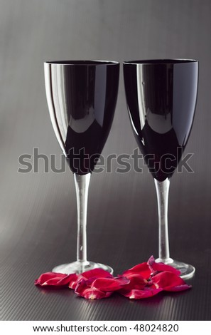 Two black glasses for wine over black background, with petals of rose