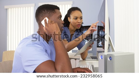 Two Black medical specialists using computer to review information together - stock photo