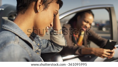 Two Black women friends texting on cell phone and leaning against car - stock photo
