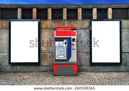 Two blank billboards attached on a wall besides a ticket machinel - stock photo